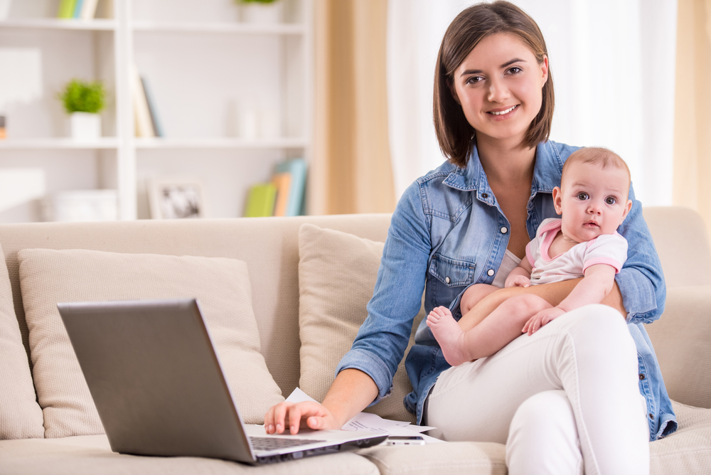 Young woman is working from home, holding baby girl on lap