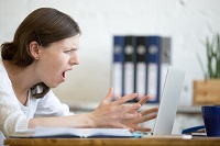 Young stressed businesswoman sitting with laptop and screaming with angry expression. Furious business person feeling irritated while using pc